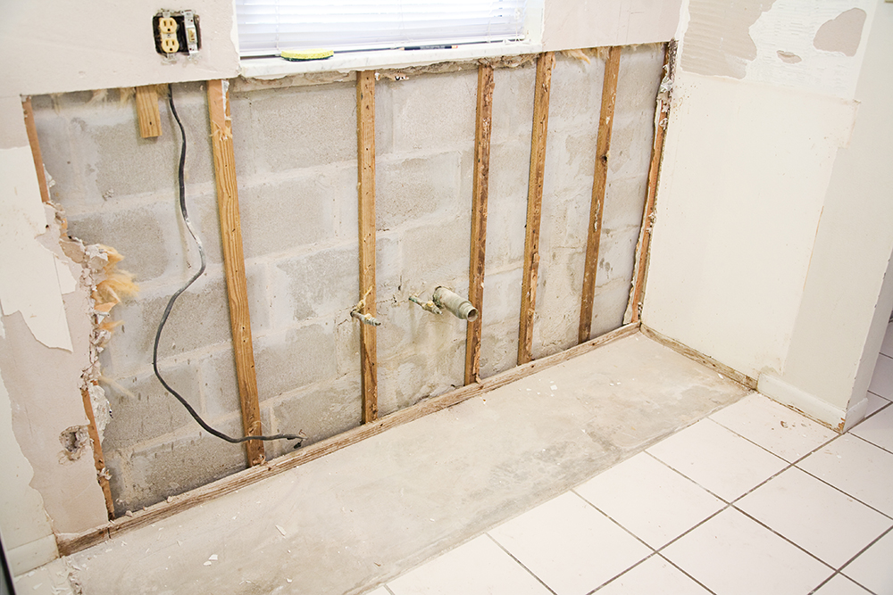 Interior of kitchen with drywall torn out because of water damage and the resulting mold.